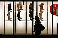 A shopper walks past the boot display in the windows of the Charlotte Russe Outlet at the Grove City Premium Outlets in Grove City, PA Thanksgiving night shortly after some of the stores opened their doors for business for Black Friday shoppers.