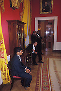 BUTLERS TAKE A BRAKE IN THE RED ROOM PRIOR TO THE BEGINNING OF A STATE DINNER.