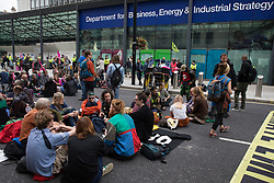 London, UK. 26th August, 2021. Environmental activists from Extinction Rebellion, Stop HS2, XR Roads Rebellion and Paid to Pollute hold crisis talks outside the Department for Business, Energy and Industrial Strategy (BEIS) following the Stop The Harm march on the fourth day of Impossible Rebellion protests. Extinction Rebellion are calling on the UK government to cease all new fossil fuel investment with immediate effect.