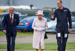 Queen Elizabeth II and the Duke of Edinburgh with their grandson, the Duke of Cambridge, as they open the new base of East Anglian Air Ambulance at Cambridge Airport.