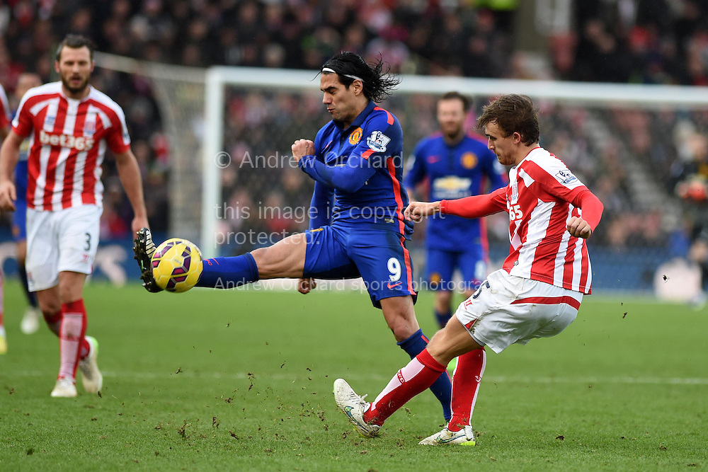 Radamel Falcao of Man Utd blocks Marc Muniesa of Stoke city. Barclays Premier league match, Stoke city v Manchester Utd at the Britannia Stadium in Stoke on Trent, Staffs on New Years Day , Thursday 1st Jan 2015. pic by Andrew Orchard. Andrew Orchard sports photography.