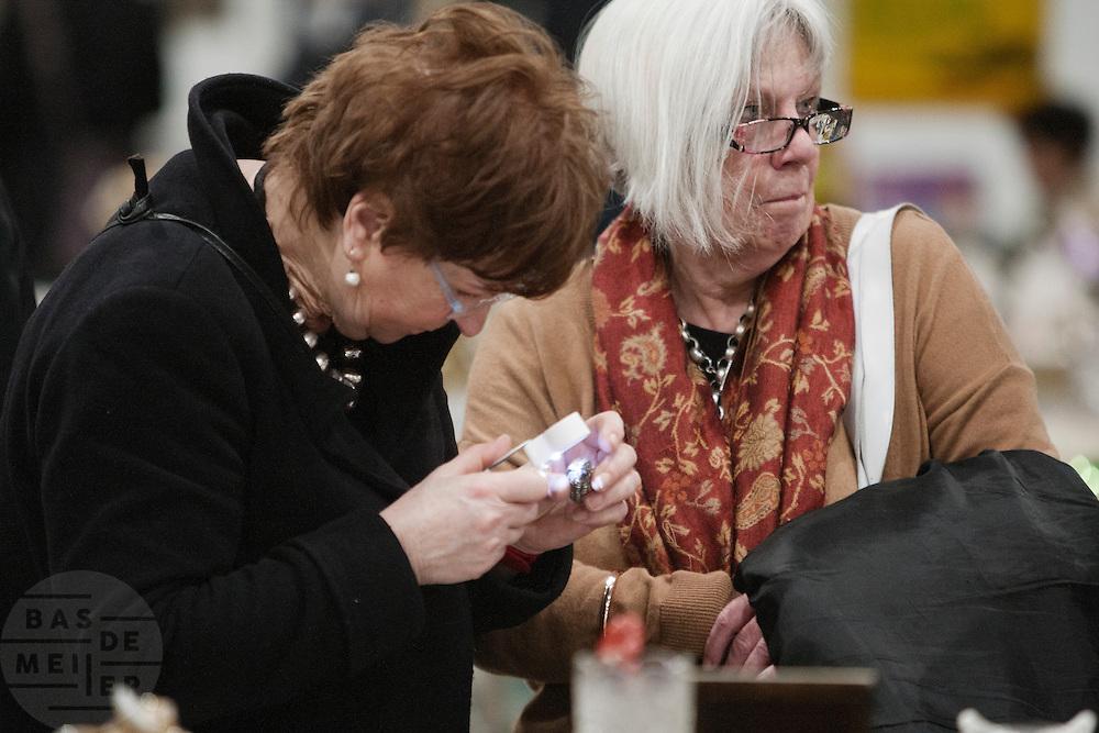 Een vrouw bekijkt op de Verzamelaarsjaarbeurs in de Jaarbeurs in Utrecht nauwkeurig naar een mogelijke aanvulling voor haar verzameling.<br /> <br /> A woman is examining an item for her collection at the collectors fair.