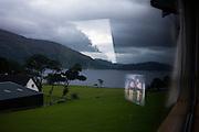 TV holiday women and bleak-looking Scottish Loch in Glencoe area, Scotland.