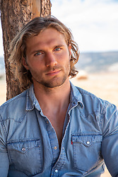 hot sexy man with long brown hair and blue eyes leaning against a wooden post