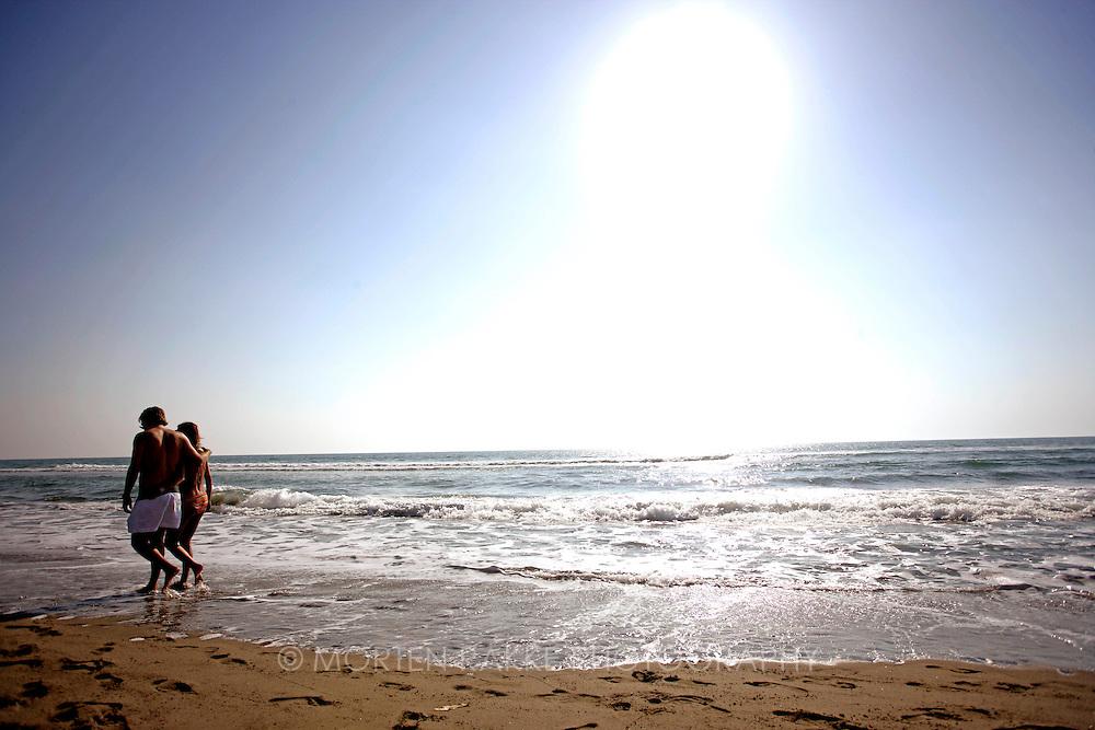 Couple walking at beach, Italy