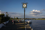 Riverside Ferry Inn sign and boating on the River Yare at Reedham on the Norfolk Broads. Visitors sit in the late sunshine at this idyllic place in this area of Britian known as East Anglia, known for its flat fenland landscape and wide skies. Reedham is one of the most popular stopping places on the Broads. The nearby village is right beside the river with pretty cottages and some shops, there are ample mooring places.