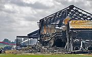 Nederland, the Netherlands, Erichem, 28-7-2017 In de dorp is een mega varkensstal uitgrbrand waarbij 20.000 dieren omgekomen zijn. De varkens zaten verdeeld over twee verdiepingen en 4 stallen. Poolse arbeiders zorgden voor de dagelijkse gang van zaken. Er is asbest vrijgekomen omdat op de daken nog eterniet, asbest, asbest dakbedekking lag. De eigenaar van deze megastal had in Duitsland een beroepsverbod als varkenshouder vanwege dierenmishandeling. Foto: Flip Franssen