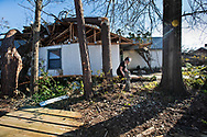 Riley Robertson  uprighting a fallen staint at her grandmothers damaged home in Lynn Haven, Florida that was hit hard by Hurricane Michael,