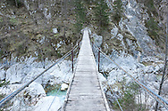 Wooden swing bridge over the River Soca on the Alpe Adria Trail, Triglav national park, Slovenia. The Alpe Adria Trail (AAT) is a 750km hiking route through Austria, Slovenia and Italy. © Rudolf Abraham