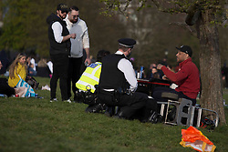 © Licensed to London News Pictures.  17/04/2021. London, UK. Police talk to a man with a speaker while members of the public making the most of the sunny weather in Primrose Hill, north London. Earlier this week Lockdown restrictions were eased to allow non essential retail and outdoor dining to reopen. Photo credit: Marcin Nowak/LNP