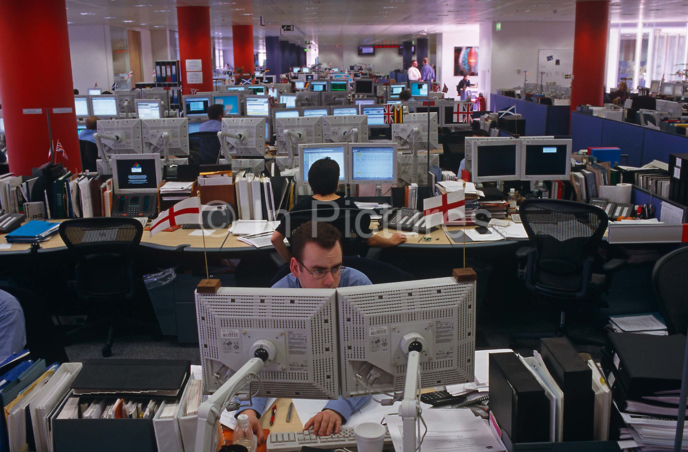 """An analyst for the Enron Corporation, the American energy company based in Houston, Texas, stares transfixed into two computer monitors in the London office at Grosvenor Place, opposite the Queen's official residence, Buckingham Palace. Two Cross of St George flags perch to the tops of the screens. Informal dress was practised in this Enron company building before its eventual bankruptcy in late 2001, Enron employed around 21,000 people  and was one of the world's leading electricity, natural gas, pulp and paper, and communications companies, with claimed revenues of $111 billion in 2000. Fortune named Enron """"America's Most Innovative Company"""" but has since become a popular symbol of willful corporate fraud and corruption."""