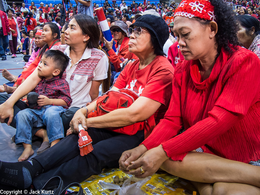 """23 FEBRUARY 2014 - NAKHON RATCHASIMA (KORAT), NAKHON RATCHASIMA, THAILAND: Red Shirt supporters listen to their leadership during a Red Shirt meeting in Korat. The United front of Democracy against Dictator (UDD or Red Shirts), which supports the elected government of Yingluck Shinawatra, staged the """"UDD's Sounding of the Battle Drums"""" rally in Nakhon Ratchasima (Korat) to counter the anti-government protests that have gripped Bangkok since November. Around 4,000 of UDD's regional and provincial coordinators along with the organization's core members met at Liptapunlop Hall inside His Majesty the King's 80th Birthday Anniversary Sports Complex in Korat to discuss the organization's objectives and tactics against anti-government protestors, which the UDD says """"seek to destroy the country's democracy."""" The UDD leadersa announced that they will march to Bangkok and demonstrate against anti-government protests led by Suthep Thaugsuban.   PHOTO BY JACK KURTZ"""