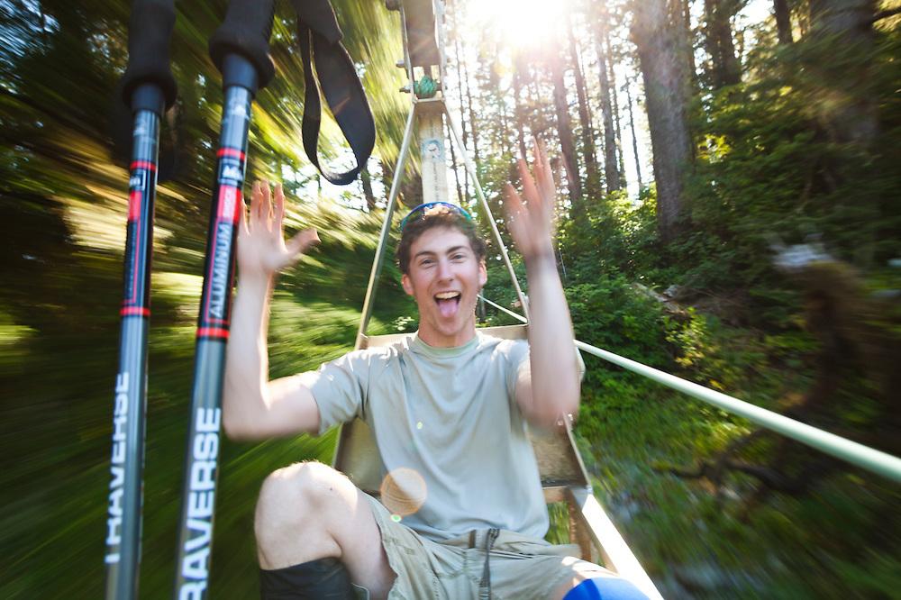 Zach Podell-Eberhardt rides the cable car across the Klanawa River, West Coast Trail, British Columbia, Canada.