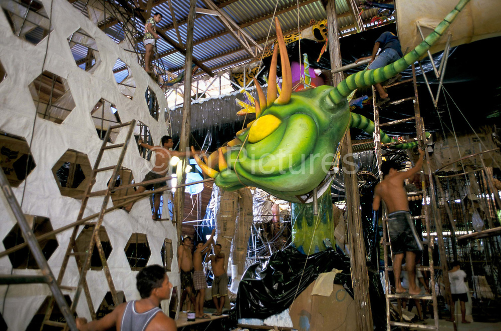 """Building a huge allegorical float inside a large warehouse for the """"Boi Bumba"""" Amazon Carnival in Parintins, Brazil. The carnival serves to celebrate and re-enact Indian traditions and perpetuate myths and legends. It has evolved over time and involves the battle between to opposing bulls, known as Garantido and Caprichoso."""