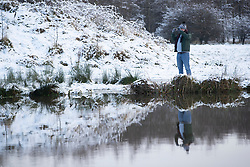 © Licensed to London News Pictures. 28/12/2020. St Helens, UK. A man takes a picture at Lyme and Wood Country park in St Helens as the North West wakes up to snow. Photo credit: Kerry Elsworth/LNP