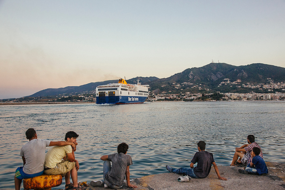 Refugees gaze after a ferry which is full of refugees heading to Athens at the port of Mytilini in Lesvos, Greece on Aug 17th, 2015.