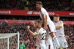 Burnley's Scott Arfield (obscured) celebrates scoring his side's first goal of the game with teammates during the Premier League match at Anfield, Liverpool.