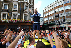 © Licensed to London News Pictures. 07/07/2018. London, UK. An England fan dressed as England Manager Gareth Southgate celebrates England's 2-0 victory over Sweden in the World Cup Quarter Finals on the roof of a car by London Bridge. Photo credit: Rob Pinney/LNP