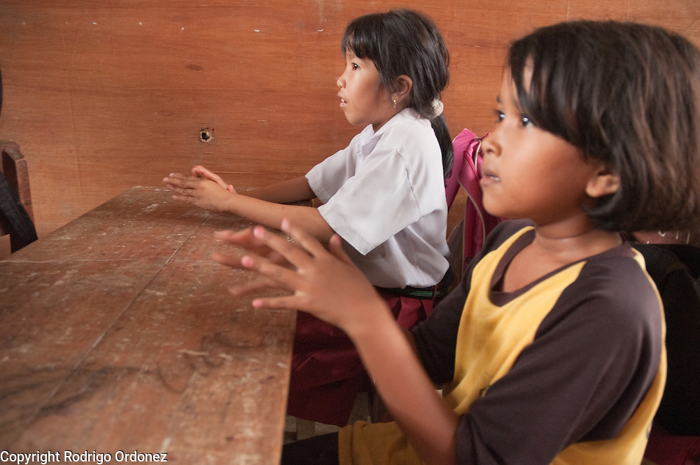 Lea, 10, (left) and other students at Elementary School 14 in Sungai Geringging follow instructions from Save the Children staff about the importance of washing hands. They are singing a song that mimics the steps to wash hands properly.