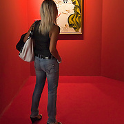 """MILAN, ITALY - SEPTEMBER 21: A womad admires """"Katharina Cornell"""", oil painting by Salvador Dali at the Exhibition preview at Palazzo Reale on September 21, 2010 in Milan, Italy. Dali is back in Milan with Il sogno si avvicina, an exhibition that takes place at Palazzo Reale  and that focus on the relationship between the great Spanish artist's visions and his favourite themes:  landscape, dream and desire."""
