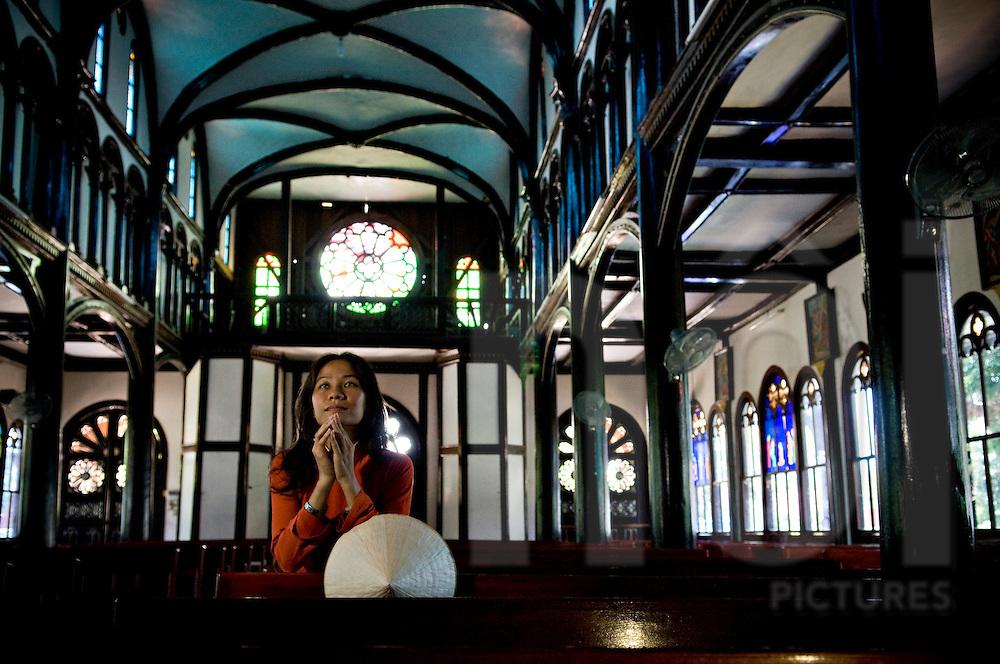A vietnamese woman praises inside Kontum's catholic church.  She's got folded hands. Vietnam, Asia