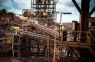 A worker looks out from the top of an Iron Ore Processing Facility ,OPF, in the Pilbara, Western Australia