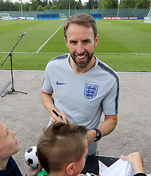 England manager Gareth Southgate signs autographs for fans during the training session at the Spartak Zelenogorsk Stadium, Repino.