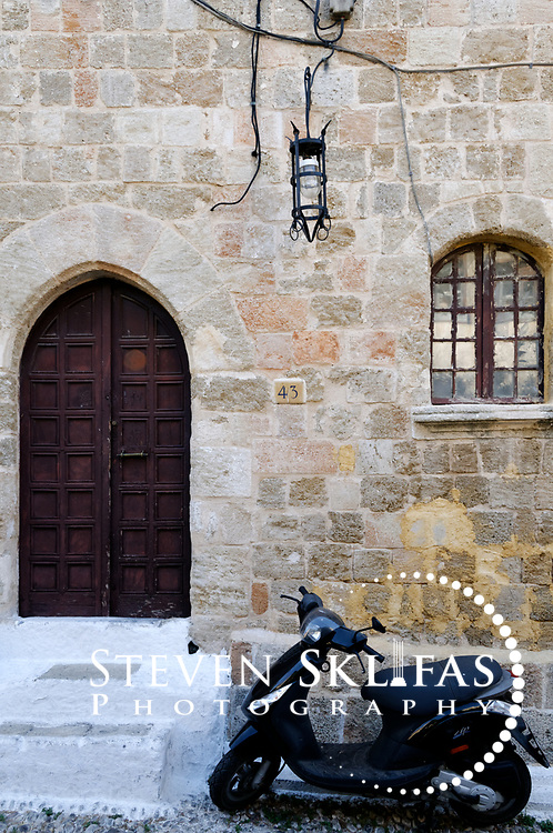 Rhodes. Greece. Motor bike or scooter in front of an old stone building with an arched doorway and windows. The scene is typical inside the old walled town of Rhodes which is a UNESCO world heritage listed site and the best preserved, oldest and largest living medieval city in Europe. The 4km defensive walls were built by the Knights of St John during the 13th to 15th century to defend Western Europe against the expanding Ottoman Empire. Within the walls are a medieval warren of small alleyways and magnificent historical buildings. The island of Rhodes is the largest of the Dodecanese Island group and one of the most popular Greek Islands.