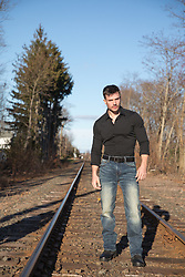 man walking on railroad tracks