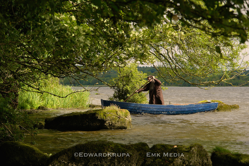 A monk paddles to the shore of an island in Ireland.