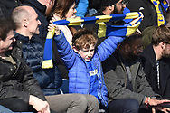A Young AFC Wimbledon fan waves his scarf during the EFL Sky Bet League 1 match between Oxford United and AFC Wimbledon at the Kassam Stadium, Oxford, England on 13 April 2019.