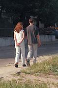 Couple age 21 strolling down sidewalk.  Gdynia Poland