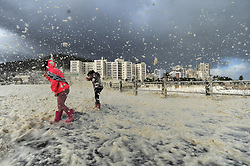 SouthAfrica - Cape Town - 13 July 2020 - Twins Liv and Eve (pink) Dorrington (7) plays in the foam. The Cape Town storm, consisting of gale-force winds, large ocean swells and disruptive snowfall continues to ravage through the Mother City on Monday 13 July. One more weather element we saw on Monday morning was huge amounts of sea foam that washed onto the coastline in Sea Point. Photographer: Armand Hough/African News Agency(ANA)