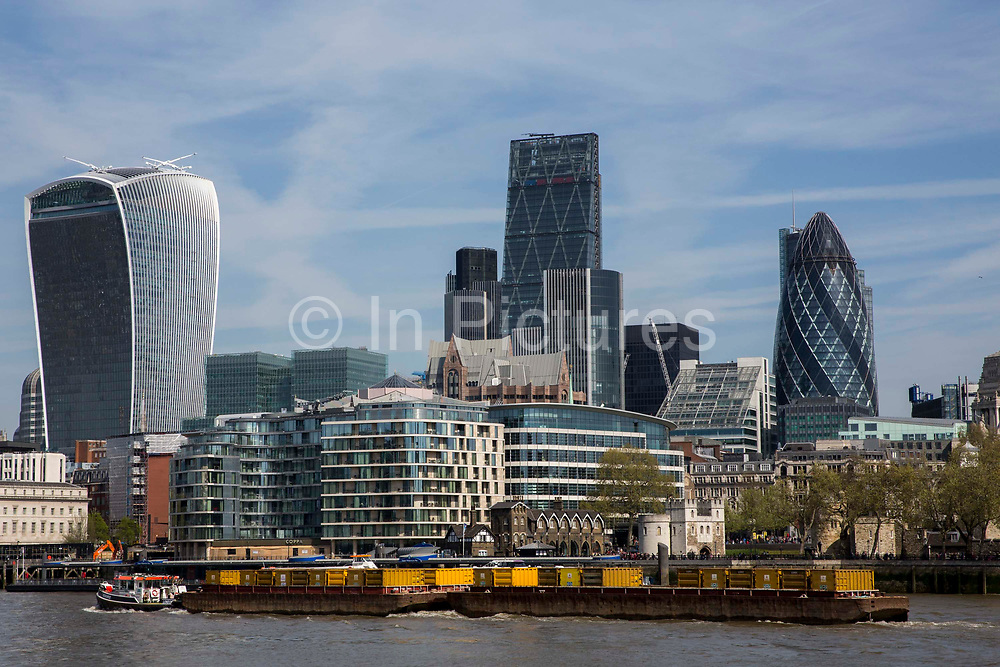 A barge carrying refuse containers passes along the Thames in front  buildings on the city of Londons skyline including the Walkie Talkie 20 Fenchurch Street and the Gherkin 30 St Mary Axe. Central London, UK. 5th May 2016