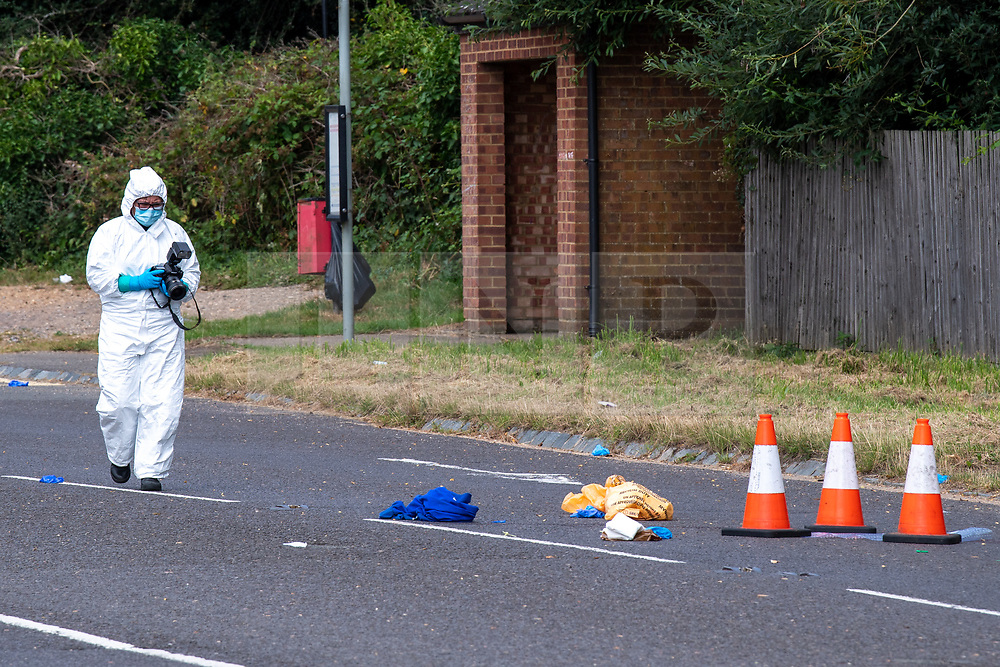 © Licensed to London News Pictures. 27/07/2021. Stoke Poges, UK. A forensic investigator takes photographs of evidence on Bells Hill in Stoke Poges, Buckinghamshire, following an assault on Monday 26 July at approximately 21:30BST. A man in his twenties suffered a serious leg injury following the assault which is understood to have involved a machete. Two men, aged 19 and 21, and a 20-year-old woman have been arrested on suspicion of section 18 wounding with intent. Photo credit: Peter Manning/LNP