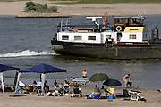 Nederland, Erlecom..Recreanten zoeken verkoeling bij de rivier de Waal. Door de lage waterstand zijn veel stranden ontstaan.Binnenvaart moet met hun lading rekening houden met de diepgang...Foto: Flip Franssen