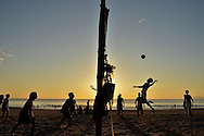 Silhouetted men play volley-ball on China beach at sunrise in Da Nang, Vietnam, Southeast Asia
