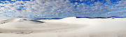 Panoramic of sand dunes at White Sands National Monument with blue skies and clouds.