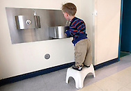 First grader Adam Kotzian has to use a stool to reach even the low water fountain at Eagleview Elementary school in Thornton, Colorado March 31, 2010.  The school has made several additions to help Adam at the school.  He and his parents are achondroplasia dwarfs but his sister Avery is not.   REUTERS/Rick Wilking (UNITED STATES)