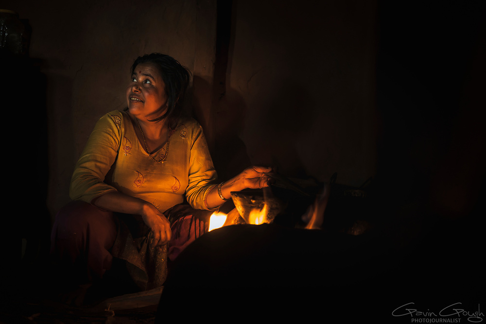 Grandmother Laxmi Phuyal tends to the fire where she cooks for her family. The fire provides heat for boiling and frying all the family's meals, which often include rice, lentils, curry and vegetables., Kakani, Nuwakot District, Nepal