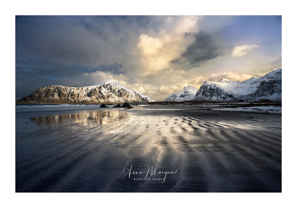 Striations in the sand a Flakstad beach, Lofoten, Norway leading towards mountains at sunset with reflected light on the wet sand
