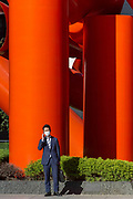 A Japanese office work or salaryman wearing a face mask talks on a cellphone in front of the Iliad Japan sculpture in Sankei Plaza, Otemachi, Tokyo, Japan. Thursday November 5th 2020