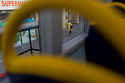 A man wearing a yellow coat appears between the yellow headrests of bus seating, on 13th November 2017, in London, England.
