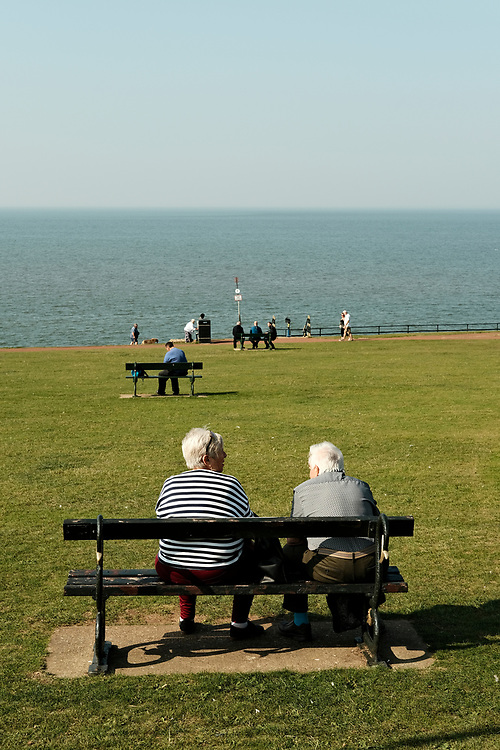 Looking towards the sea, three benches across the grass on Hunstanton sea front. An older lady & gentleman sit watching out to sea on the last hot day of the Summer in Hunstanton Norfolk, the first summer in the UK during the COVID-19 pandemic.<br /> Photo by Jonathan J Fussell, COPYRIGHT 2020