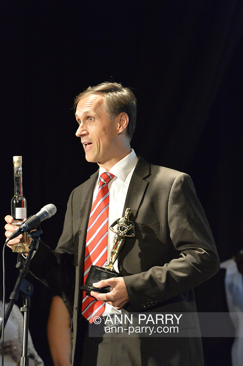 "Bellmore, New York, USA. July 21, 2016. BERNHARD RAMMERSTORFER accepts ""Alan Fortunoff Humanitarian Award"" for documentary ""Taking the Stand"" which he was director, producer and writer of, at The19th Annual Long Island International Film Expo Awards Ceremony, LIIFE 2016, held at the historic Bellmore Movies. Rammerstofer is holidng a bottle of Organic Austrian Schnaps Plum Self-Made by Ernst Blajs, a present he gave to LIIFE. LIIFE was called one of the 25 Coolest Film Festivals in the World by MovieMaker Magazine."
