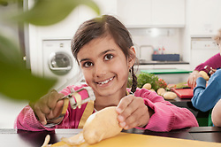 Schoolgirl peeling potatoes with peeler in home economics class, Bavaria, Germany