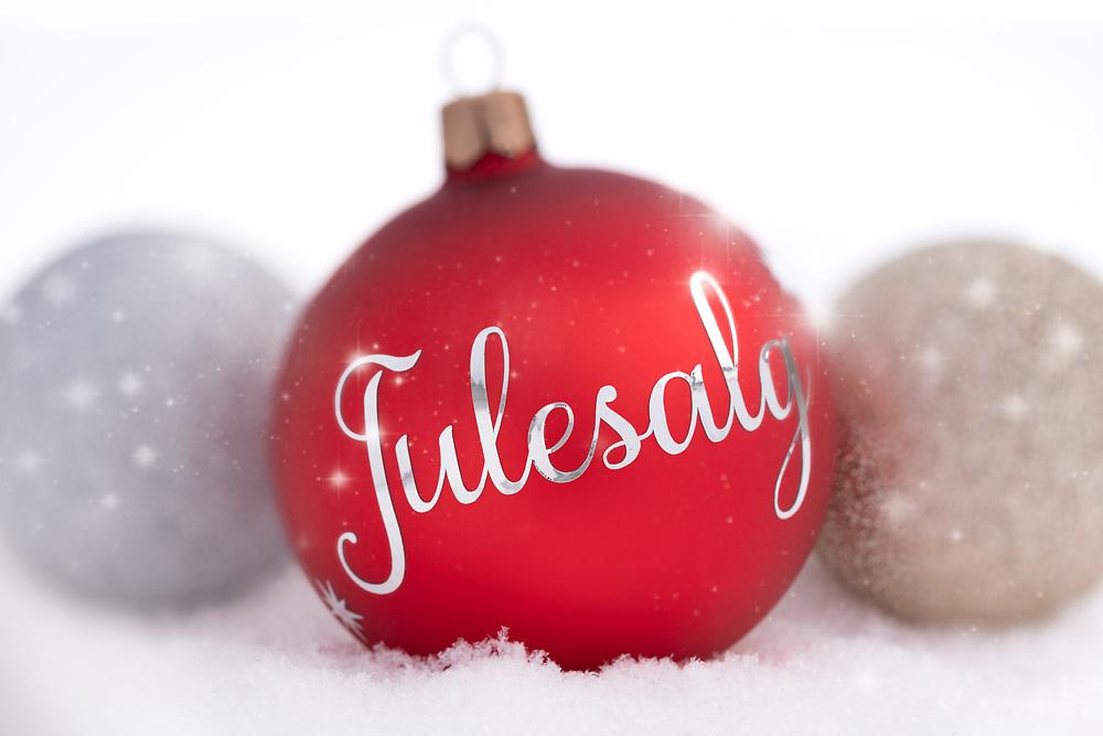 Rød julekule med sølvfarget norsk tekst «Julesalg». På hvit snø flankert av glitrende julekuler.