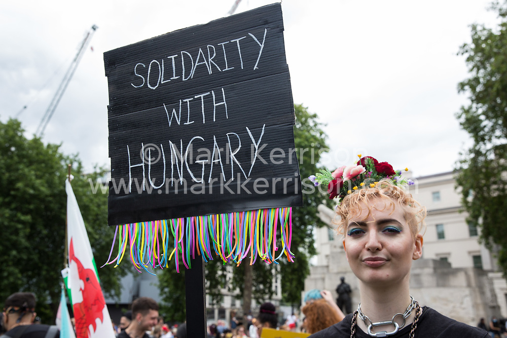 A protester holds a sign reading Solidarity With Hungary as thousands of people assemble to take part in a London Trans+ Pride march from the Wellington Arch to Soho Square on 26th June 2021 in London, United Kingdom. Hungary has introduced legislation banning schools from using materials seen as promoting homosexuality. London Trans+ Pride is a grassroots protest event which is not affiliated with Pride in London and focuses on creating a space for the London trans, non-binary, intersex and GNC community to come together to celebrate their identities and to fight for their rights.