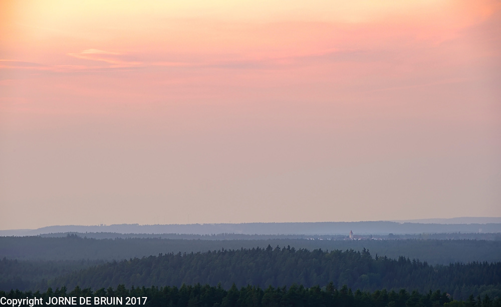 Sunset on the northern bavarian forest with a small town in the distance.