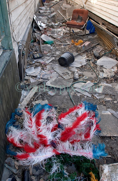 25 Oct,  2005.New Orleans, Louisiana. Hurricane Katrina aftermath.<br /> The 8th ward lies in ruins following Katrina's devastating floods. A mardi gras indian's headress lies in the dirt between two houses. <br /> Photo; ©Charlie Varley/varleypix.com